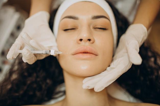 Kobieta robi zastrzyki u kosmetologa