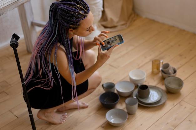Kobieta robi zdjęcia ceramicznych naczyń kuchennych w domu