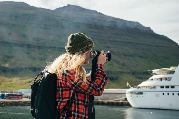 Kobieta robi zdjęcia epickiego statku wycieczkowego po fiordzie