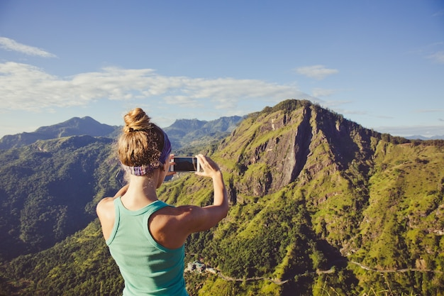 Kobieta robi zdjęcia gór rano ze szczytu góry