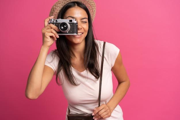 Kobieta robi zdjęcia trzymając aparat fotograficzny, odizolowane na różowo.