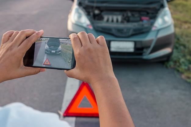 Kobieta robi zdjęcie do silnika samochodu