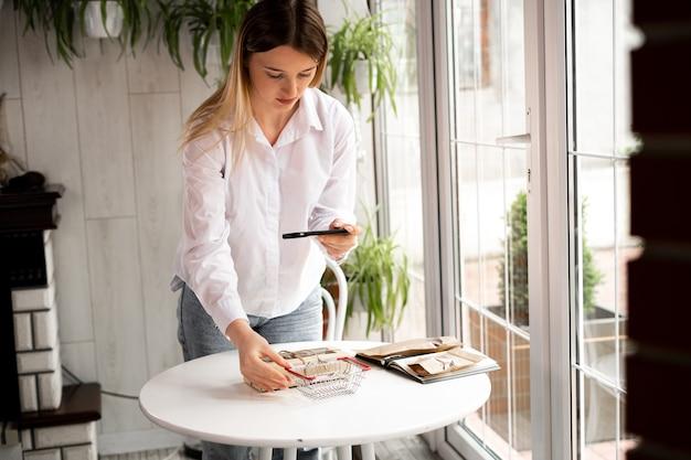 Kobieta robi zdjęcie kreatywnych produktów swojego sklepu internetowego. mały biznes i dziewczyna w kawiarni. produkty dla wegan. businesswoman kręci treści na smartfonie dla sklepu.