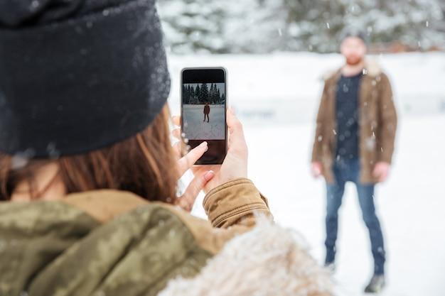Kobieta robi zdjęcie mężczyzny na zewnątrz