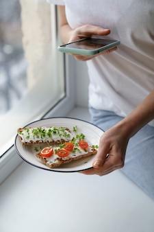 Kobieta robi zdjęcie na smartfonie, trzymając talerz z chrupiącym chlebem żytnim z serem i mikro zieleniną