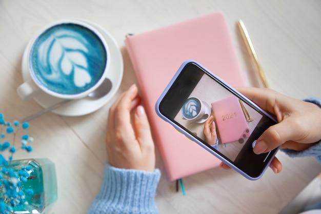 Kobieta robi zdjęcie niebieskiej kawy latte, różowego kolorowego planera 2021 i złotego pióra na swoim smartfonie. ludzie i technologia. robienie zdjęć do publikowania i udostępniania w mediach społecznościowych. koncepcja blogowania.