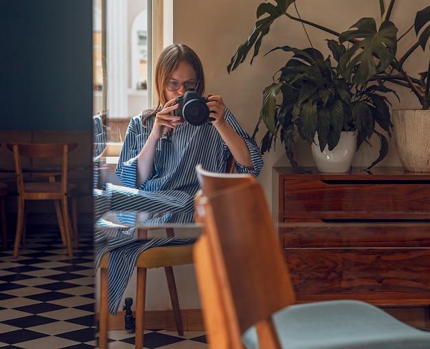 Kobieta robi zdjęcie siebie odbijającej się w lustrze w nowoczesnej kawiarni przy świetle dziennym i zielonych roślin...