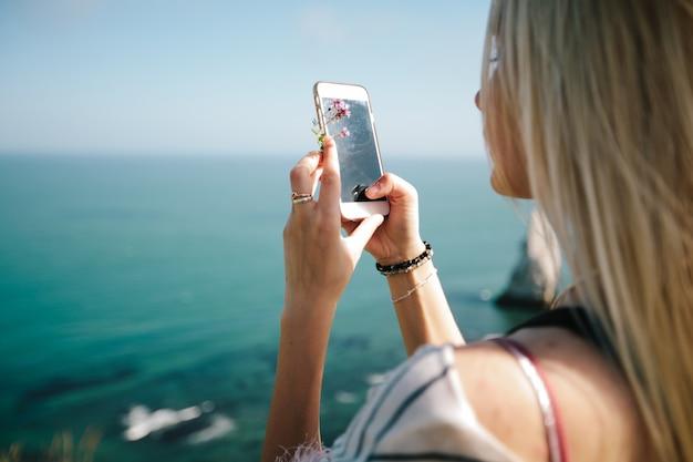 Kobieta robi zdjęcie widok z góry na zatokę i alabastrowy klif zatoki etretat we francji