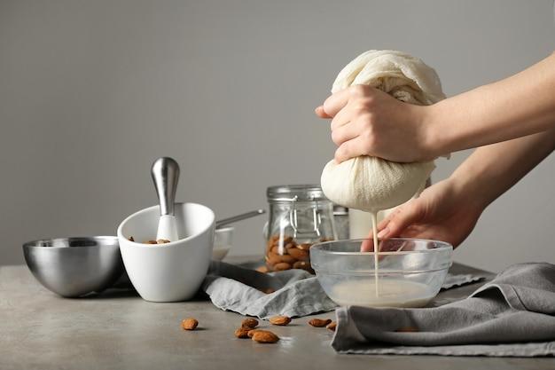 Kobieta robi zdrowe mleko migdałowe w kuchni