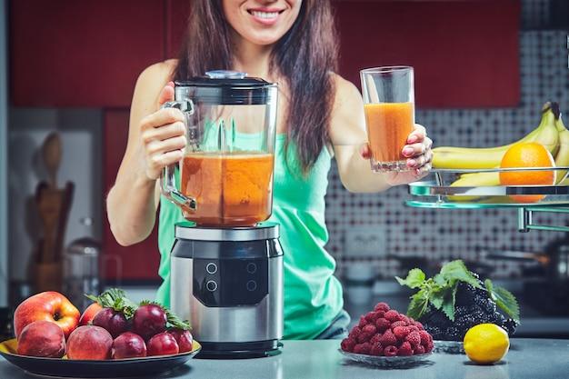 Kobieta robi zielonego smoothie w kuchni. skoncentruj się na blenderze.