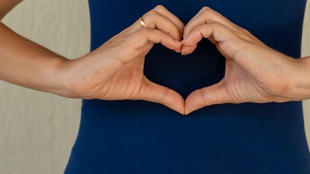 Kobieta robiąca ręce w kształcie serca serce ubezpieczenie zdrowotne odpowiedzialność społeczna darowizna