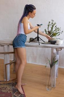 Kobieta robiąca zdjęcia ceramicznym przyborom kuchennym