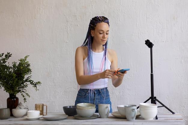 Kobieta robiąca zdjęcia do swojej firmy przy użyciu naczyń kuchennych