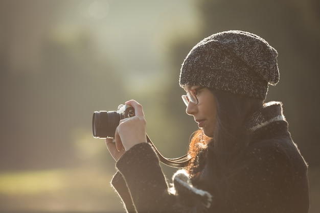 Kobieta robienia zdjęć aparatem cyfrowym w parku