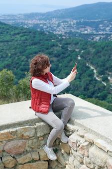 Kobieta robienia zdjęć swoim inteligentnym telefonem w górskie poszukiwanie