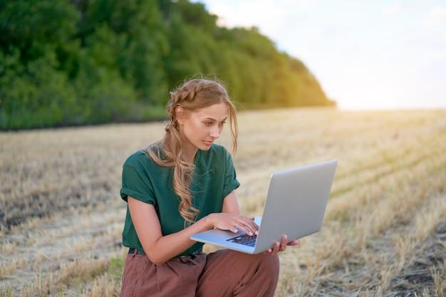 Kobieta rolnik inteligentne rolnictwo stojąca ziemia uprawna uśmiechnięta za pomocą laptopa kobieta agronom specjalista badania monitorowanie danych agrobiznesu
