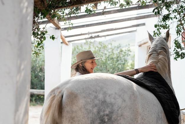 Kobieta rolnik kładzie siodło na jej koniu na ranczo