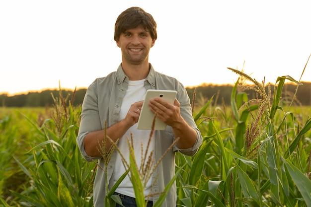 Kobieta rolnik monitorująca uprawę kukurydzy za pomocą cyfrowego tabletu
