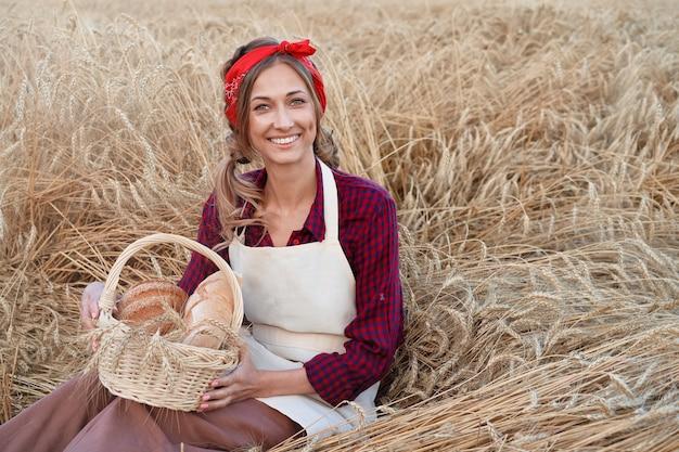 Kobieta rolnik posiedzenia pola pszenicy kobieta piekarz gospodarstwa wiklinowy kosz chleb produktu