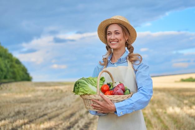 Kobieta rolnik słomkowy kapelusz fartuch stojący pole uprawne uśmiechnięta kobieta agronom specjalista rolnictwo agrobiznes szczęśliwy pozytywny pracownik kaukaski pole rolne