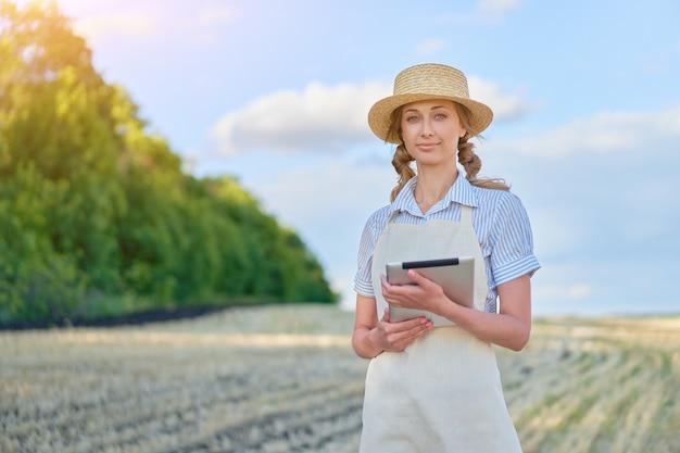 Kobieta rolnik słomkowy kapelusz inteligentne rolnictwo stojące pole uprawne uśmiechnięte za pomocą cyfrowego tabletu kobieta agronom specjalista badania monitorowanie danych agrobiznesu