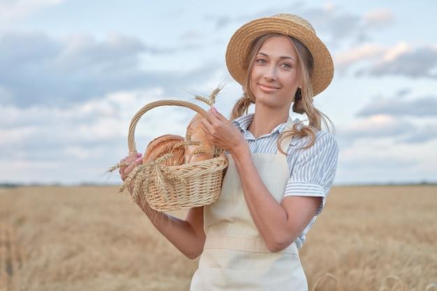 Kobieta rolnik stojący pszenica pole rolne kobieta piekarz trzymający wiklinowy kosz chleb produkt