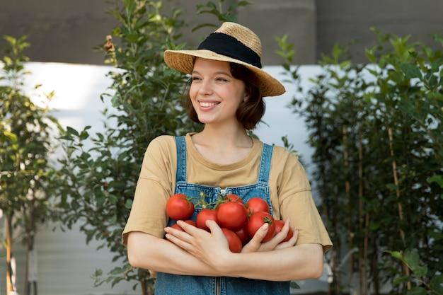 Kobieta rolnik trzymająca pomidory