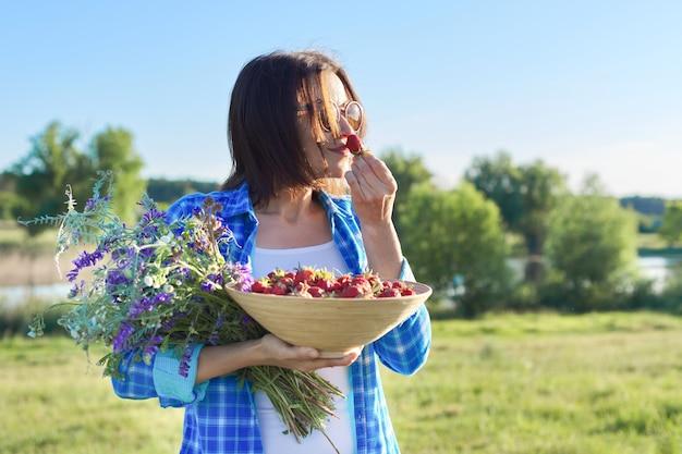 Kobieta rolnik z miską świeżo zebranych truskawek i bukietem polnych kwiatów. natura tło, wiejski krajobraz, zielona łąka, wiejski styl