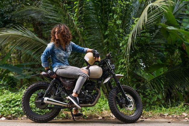 Kobieta rowerzysta jazdy motocyklem racer kawiarni