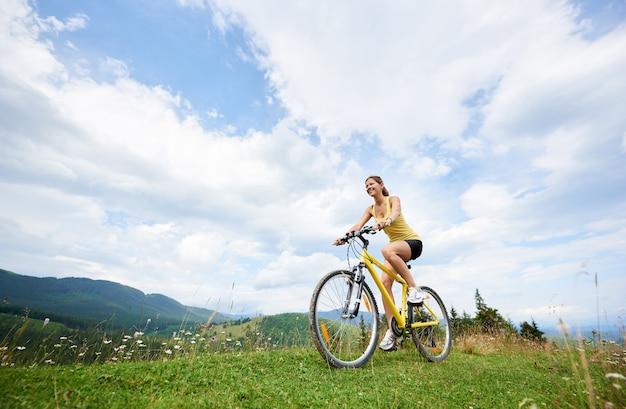 Kobieta rowerzysta na rowerze na żółty rower górski na trawiastym wzgórzu, ciesząc się letni dzień w górach