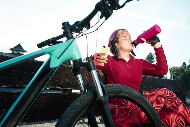 Kobieta rowerzysta odpoczywa i pije wodę z butelki trzyma w ręku telefon komórkowy