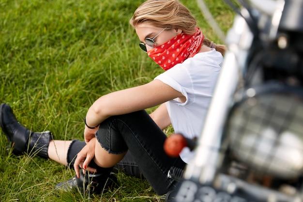 Kobieta rowerzysta siedzi na trawie obok motocykla