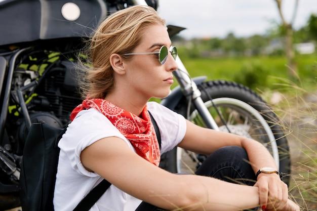 Kobieta rowerzysta siedzi obok motocykla