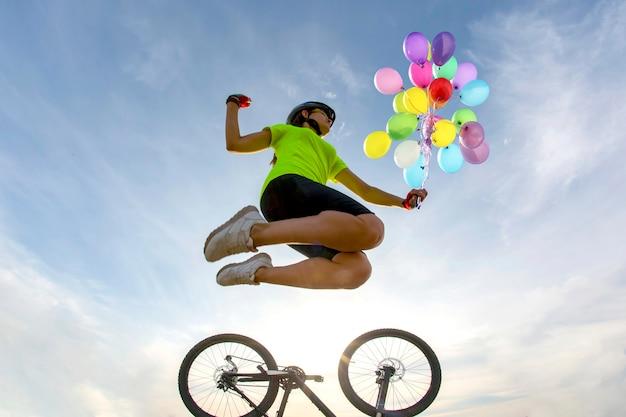 Kobieta rowerzysta skacze do nieba z balonów na miejsce na rower