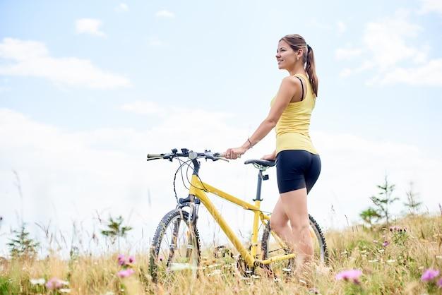 Kobieta rowerzysta stojący na trawiastym wzgórzu z żółtym rowerze górskim, ciesząc się letni dzień w górach