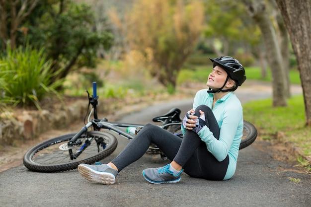 Kobieta rowerzysta w bólu, trzymając jej rannych nóg