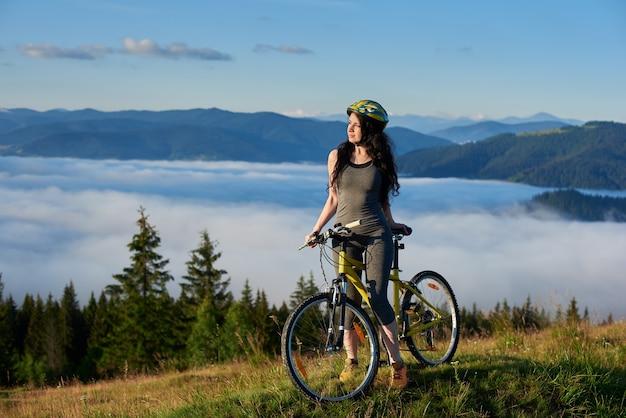 Kobieta rowerzysta z rowerem w górach