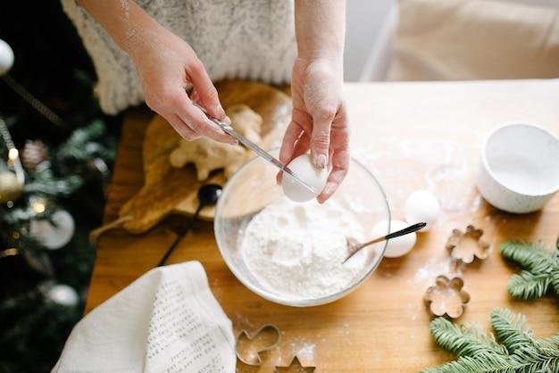 Kobieta rozbija jajko i dodaje do mąki. gotowanie procesowe.