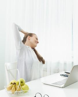 Kobieta rozciąga ramiona, ugniata plecy ze zmęczenia.