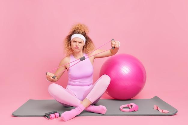 Kobieta rozciąga się na ekspanderze siedzi ze skrzyżowanymi nogami na macie fitness wykonuje ciężkie trudne ćwiczenia ubrana w strój sportowy
