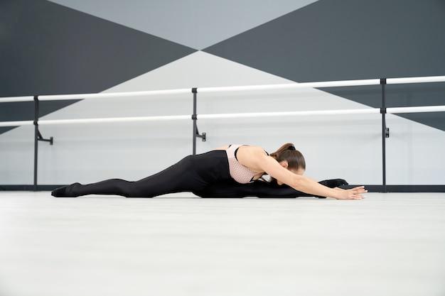 Kobieta rozciąga się z głową na kolanie
