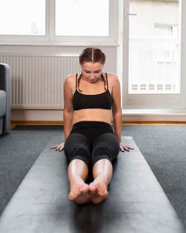 Kobieta, rozciągając nogi w pomieszczeniu