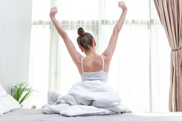 Kobieta, rozciągając się w łóżku w domu i próbując obudzić się wcześnie rano, aby rozpocząć nowy dzień