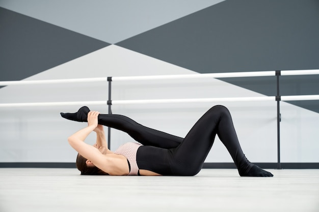 Kobieta rozciągająca nogę na podłodze