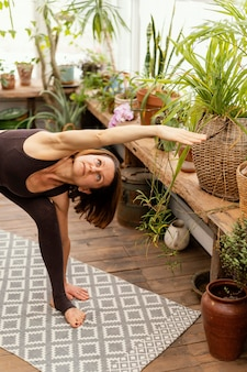 Kobieta rozciągająca się w pokoju z roślinami