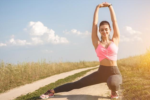 Kobieta rozciągająca się w polu na słonecznym tle