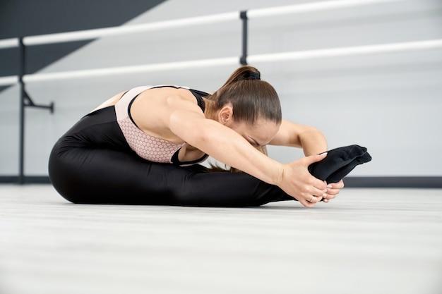 Kobieta rozciągająca się z głową na kolanach