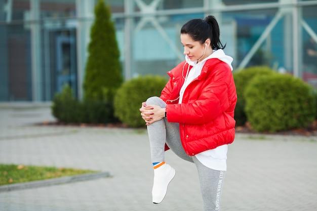 Kobieta, rozciąganie ciała, robienie ćwiczeń na ulicy