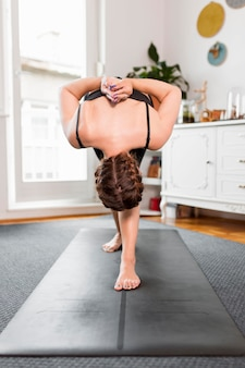 Kobieta rozciąganie jej pleców jogi w domu koncepcja