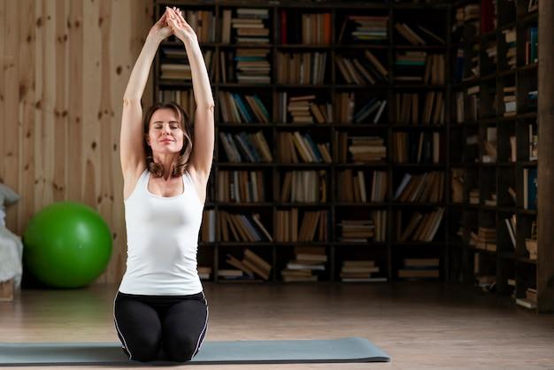 Kobieta rozciąganie na matę do jogi